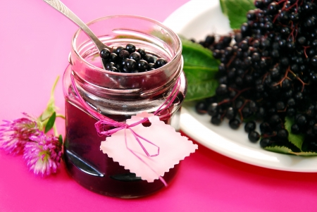 jar of homemade elderberry confiture and fresh fruits on pink background