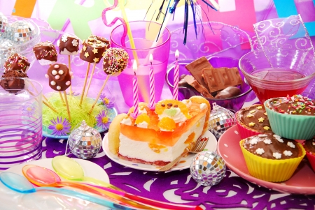 child food: colorful decoration of birthday party table with cake and sweets for child Stock Photo