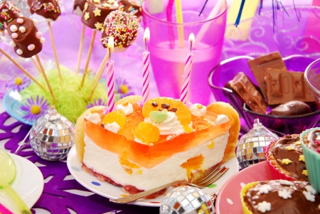 children party: colorful decoration of birthday party table with cake and sweets for child Stock Photo