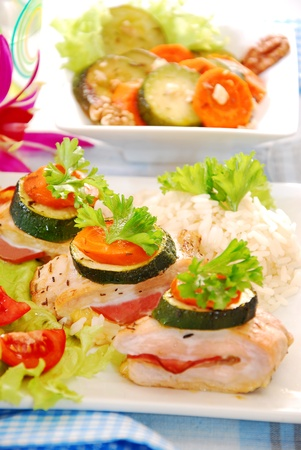 baked chicken breast filled with parma ham and cheese served with rice and zucchini-carrot salad Stock Photo - 15821854