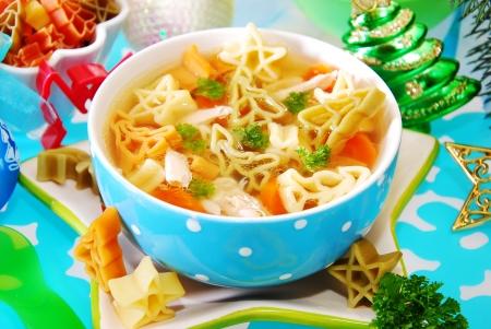 sopa de pollo: plato de sopa de pollo con pasta Navidad forma de símbolos para niño Foto de archivo