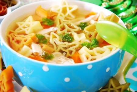 meat soup: bowl of chicken soup with christmas symbols shape pasta for child