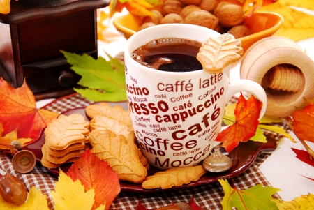 cup of coffee and cookies in leaf shape on table with autumn decoration