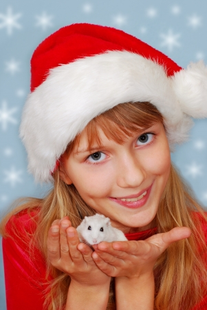 young happy girl in santa hat holding in hands little white hamster