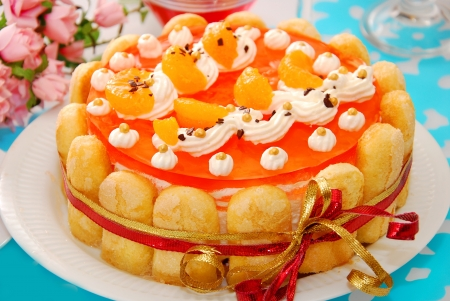torte: orange jelly and whipped cream torte garnished around with sponge fingers in charlotte style  Stock Photo