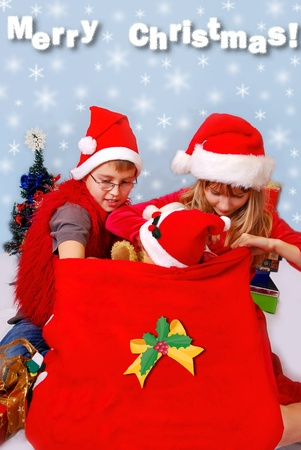 young boy and girl in red hats looking into santa`s sack for favorite christmas gifts  photo