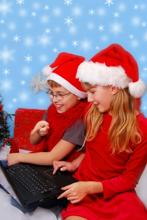 young boy and girl in santa hat with laptop choosing perfect christmas gifts in internet  photo