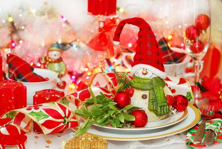 christmas table set with funny snowman in red cap on the plate photo