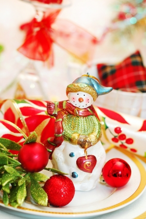 christmas table set with ceramic snowman figurine on the plate photo