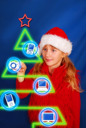 young girl in santa hat choosing gift on virtual christmas tree photo
