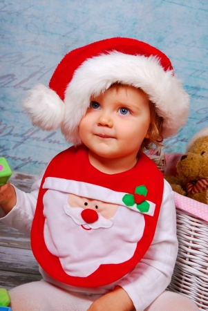 portrait of cute baby girl in red santa hat playing with toys photo