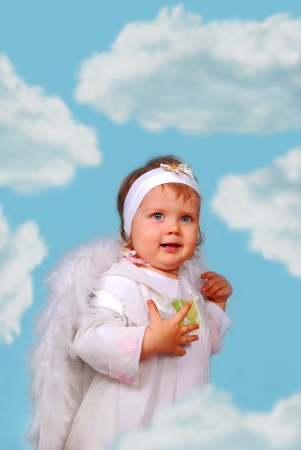 little baby girl with white wings as angel amoung the clouds photo
