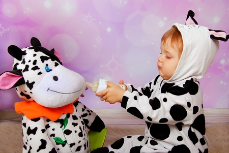 baby girl in cow costume feeding milk bottle big cow mascot photo