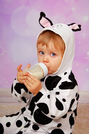 studio happy overall: little baby girl in cow costume drinking milk from bottle Stock Photo