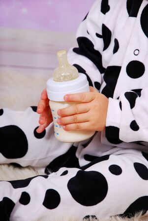 hands of baby girl in cow costume holding milk bottle photo