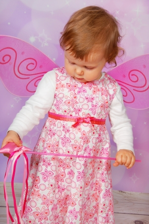 bewitch: adorable baby girl with fairy wings and wand on pink  background Stock Photo
