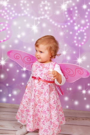 bewitch: adorable baby girl with fairy wings on pink shining background