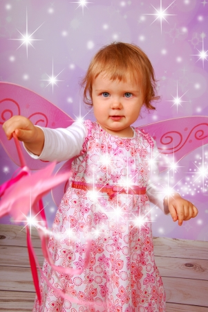 bewitch: adorable baby girl with fairy wings and wand on pink shining background