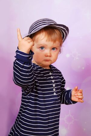 angry baby: little baby girl in striped dress and hat pointing of the finger