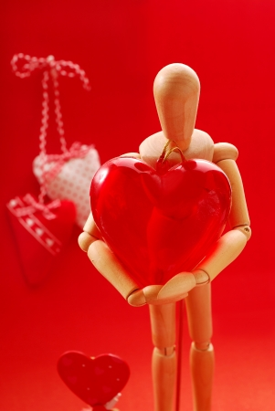 wooden mannequin: wooden model holding big plastic heart as gift for valentine