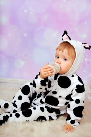 little baby girl in cow costume drinking milk from bottle photo