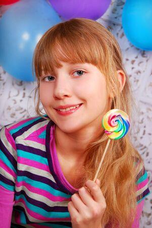 girl licking: beautiful young girl having fun with colorful lollipop Stock Photo