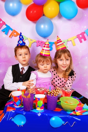 children sitting at the table and celebrating  first birthday of baby girl photo