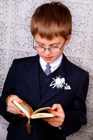 portrait of the boy going to the First Holy Communion holding prayer book and a rosary photo
