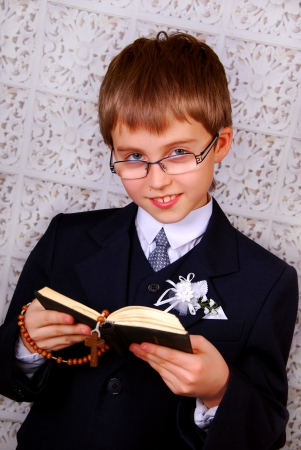 portrait of the boy going to the first holy communion  with prayer book and rosary photo