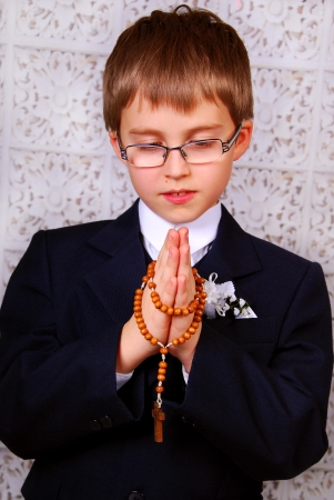 portrait of the boy going to the first holy communion praying with a rosary
