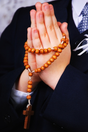 Hands of the boy going to the First Holy Communion set in amen with a rosary