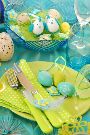 easter table decoration with eggs on the plate in pistachio and turquoise colors photo