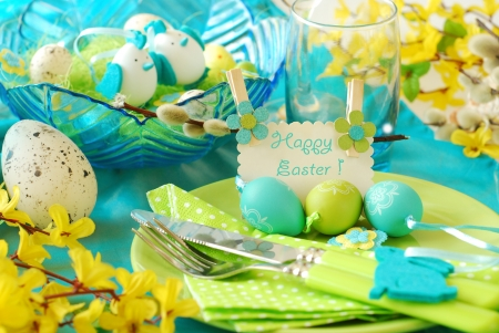 easter table decoration with greeting card on the plate in pistachio and turquoise colors