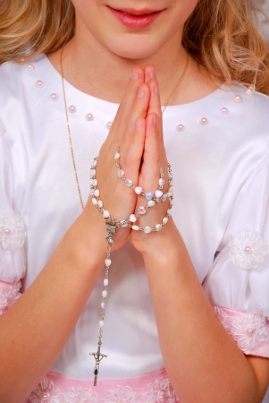first day: hands of the girl praying with rosary in day of the first holy communion Stock Photo