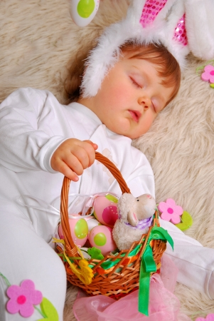 sleeping baby girl in easter bunny costume holding  basket with eggs and sheep photo