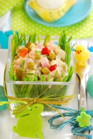 fresh vegetable salad with ham and mayonnaise in glass bowl decorated with chives for easter photo