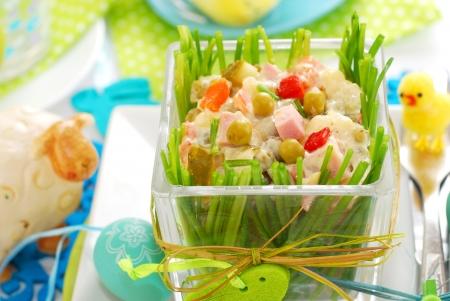 ensalada rusa: Ensalada de verduras frescas con jamón y mayonesa en un tazón de vidrio decorado con cebollines de Pascua