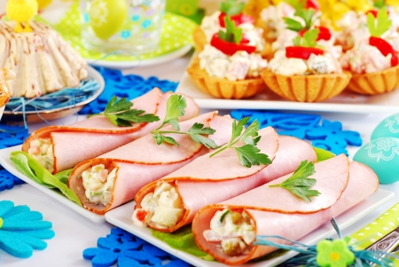 ham rolls stuffed with vegetable salad and mayonnaise and other dishes as appetizer for easter breakfast Standard-Bild