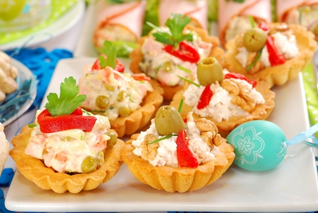 salty mini tartlets stuffed with walnut cheese and olives or vegetable salad as appetizer for easter breakfast photo
