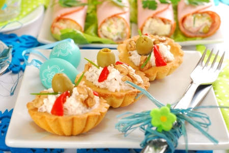 salty mini tartlets stuffed with walnut cheese and olives as appetizer for easter breakfast photo