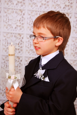 young boy holding the candle in day of the first holy communion Stockfoto