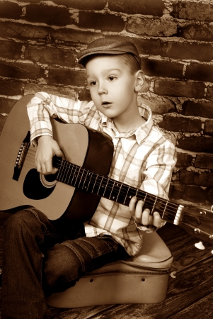 vintage style of little boy playing guitar sitting on a brick wall background photo