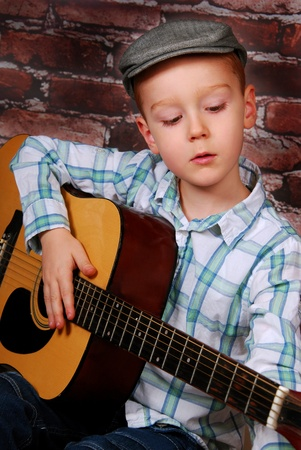 little boy playing guitar sitting on a brick wall background photo