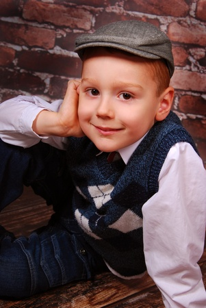 elegant little boy in golfer cap and wool vest sitting on a brick wall background photo