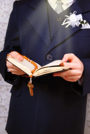 praying boy going to the first holy communion holding prayer book and rosary Stock Photo - 18180690
