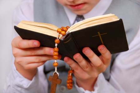 hands of praying boy going to the first holy communion holding prayer book and rosary