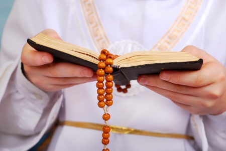 hands of praying boy going to the first holy communion holding prayer book and wooden rosary photo