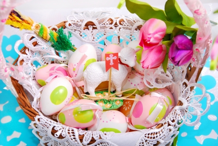 easter basket with painted eggs ,sheep figurine and tulips photo