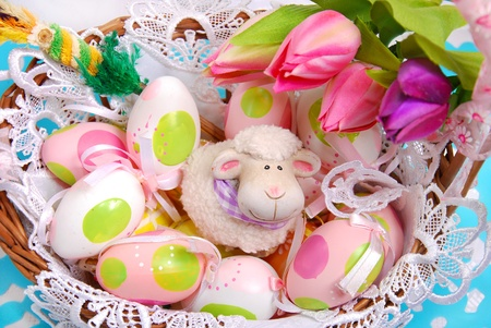 easter basket with painted eggs and funny sheep figurine photo