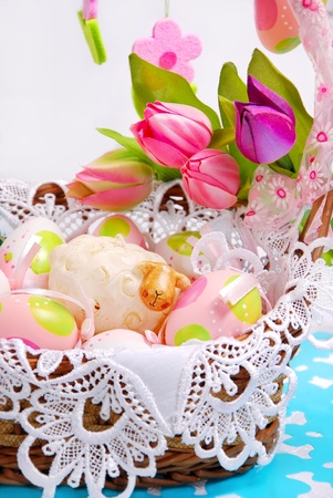 easter basket with painted eggs , sheep figurine and tulips photo